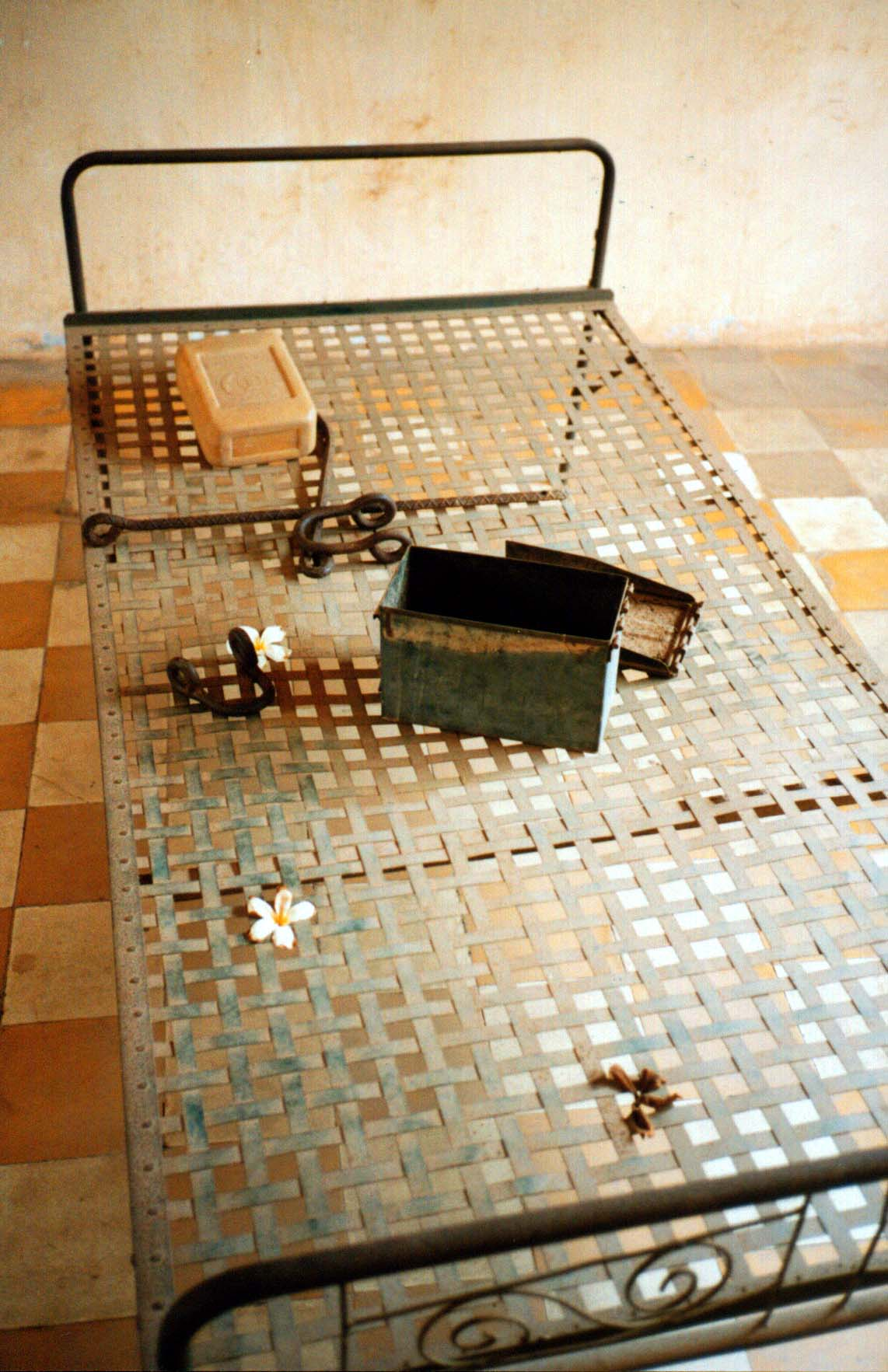 At S-21, a bed once used for torture now has flowers scattered on it (Phnom Penh, Cambodia) - Page 170